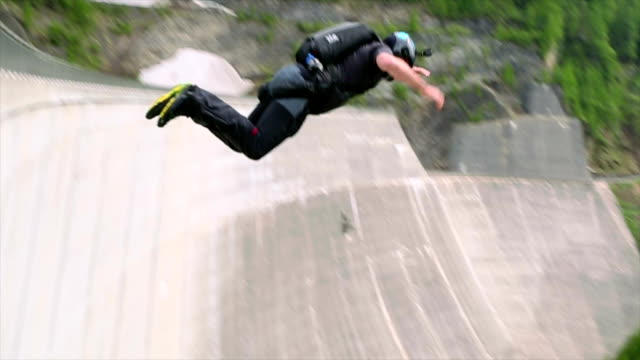 base jumper plunges down concrete dam face - base jumping video stock e b–roll