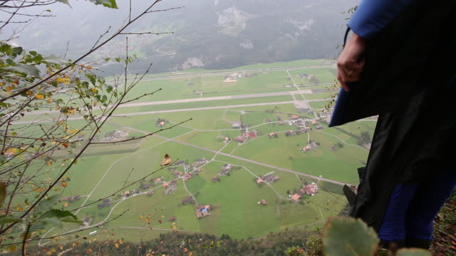 base jumper plunges from cliff edge, mountains - base jumping video stock e b–roll
