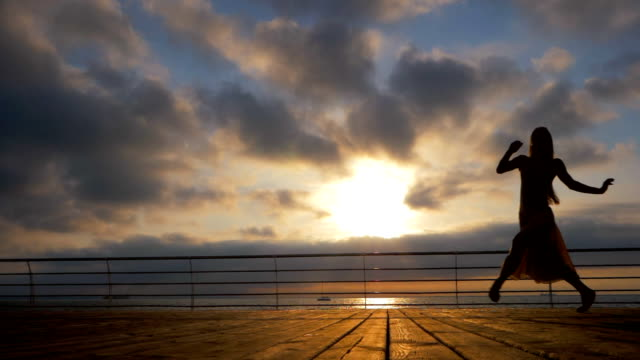 Jumping ballerina in beige silk dress and pointe on embankment above ocean or sea beach at sunrise or sunset. Silhouette of young beautiful blonde woman with long hair practicing stretching and classic exercises. Epic jump. SLOW MOTION video
