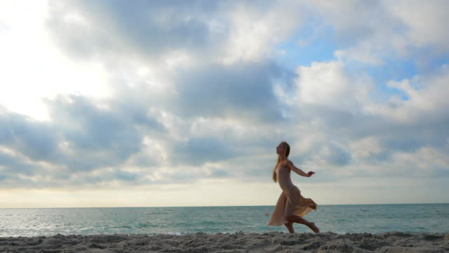 Jumping ballerina in beige silk dress and pointe on sand beach near sea at sunrise or sunset. Silhouette of young beautiful blonde woman with long hair practicing stretching and classic exercises. Epic jump. SLOW MOTION video