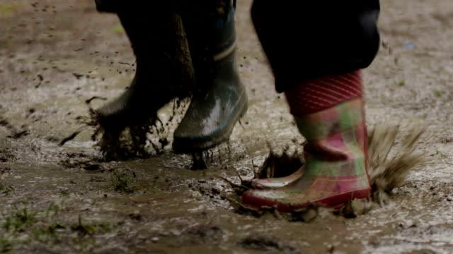 vídeos de stock e filmes b-roll de saltar em uma poça de lama com botas de chuva - poça