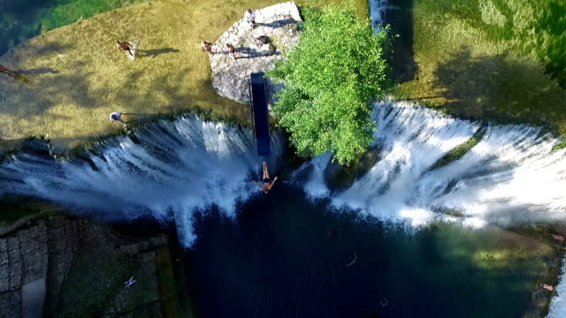 Jumping into river over waterfall in Jajce. Aerial View Slow Motion. Young Man Jumps off Cliff video