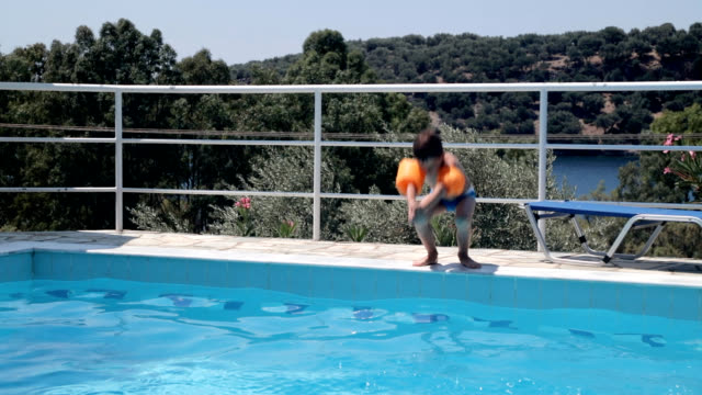Jumping into swimming pool Boy with water wings jumping into swimming pool, handheld shot only boys stock videos & royalty-free footage