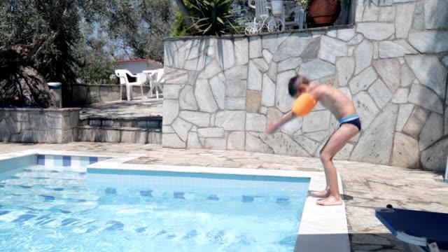 jumping into swimming pool - solo bambini maschi video stock e b–roll