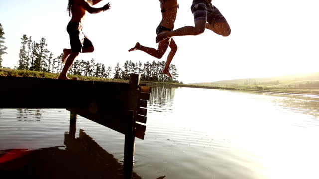 Jumping into the lake from a jetty Jumping into the lake from a jetty in slow motion swimming stock videos & royalty-free footage