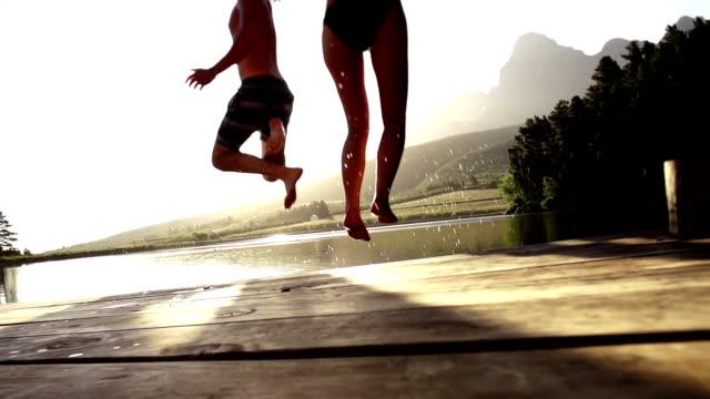 jumping into the water from a jetty - dalgakıran stok videoları ve detay görüntü çekimi