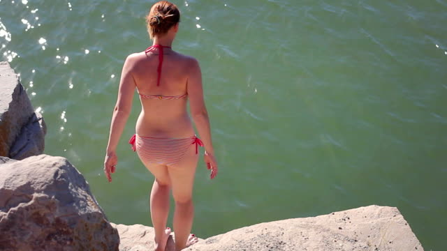 Jumping into water Girl in Bikini dives into the water from the rocks cliff jumping stock videos & royalty-free footage