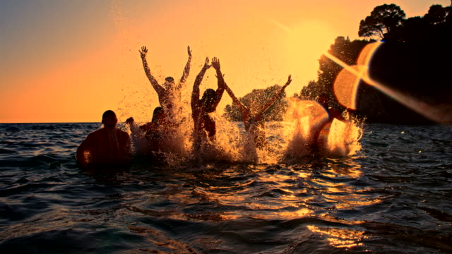 SLO MO Jumping Out Of The Sea At Dusk HD1080p: SLOW MOTION shot of a group of young people jumping out of the sea with their arms up in the air while swimming at dusk. The footage was shot in raw. Also available in 4K resolution. recreational pursuit stock videos & royalty-free footage