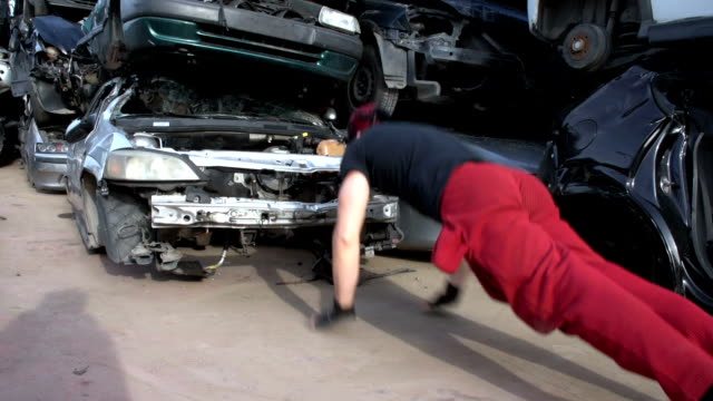 Jumping push up on one hand at junkyard (slowmotion) FDV An athlete decides to train in a junkyard pushing up on a completely destroyed car bodyweight training stock videos & royalty-free footage