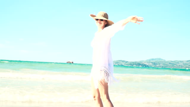 junge blonde frau mit hut und weißer tunika bewegt sich auf thailändischem strand video