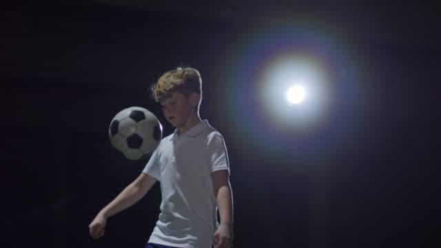 stockvideo's en b-roll-footage met junior atleet voetbal in schaatshal jongleren - sportcompetitie