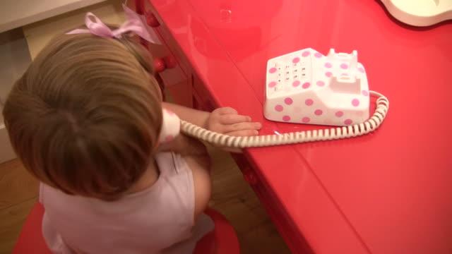 (hd1080i) junior executive competenze di telefono;/a figlio/a si parla sul telefono giocattolo - bassino video stock e b–roll