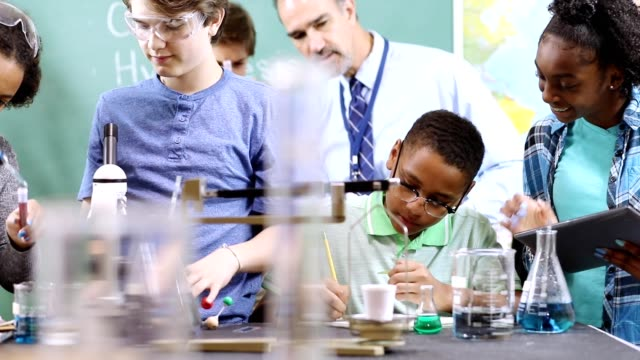Junior high age school students conduct science experiments in classroom.
