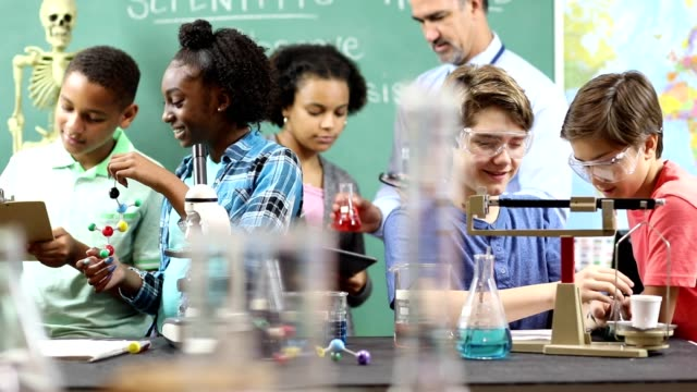Junior high age school students conduct science experiments in classroom. Junior high, high school age multi-ethnic group of students work on science experiments in school classroom setting.  STEM topics.  Laboratory glassware, microscope, scales. stem research stock videos & royalty-free footage