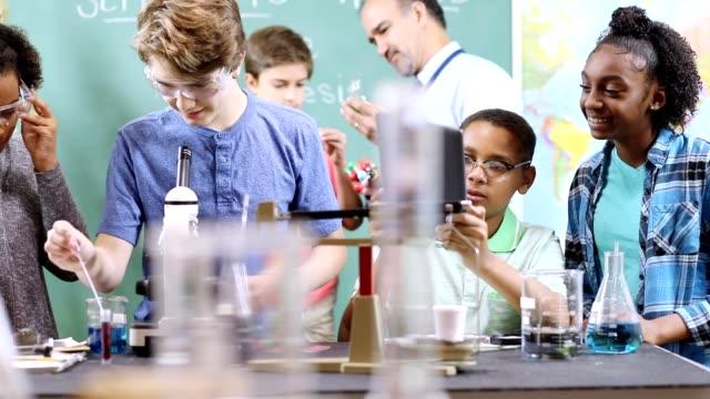 vídeos y material grabado en eventos de stock de los estudiantes de secundaria realizan experimentos científicos en el aula. - escuela media