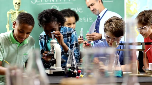 Junior high age school students conduct science experiments in classroom. video