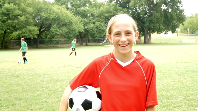 Junior High school age female soccer player tossing ball on sidelines during game video