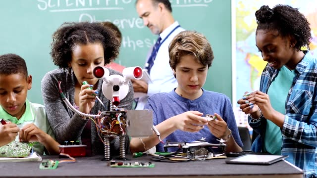 Video Junior high school age students build robot in technology, engineering class.