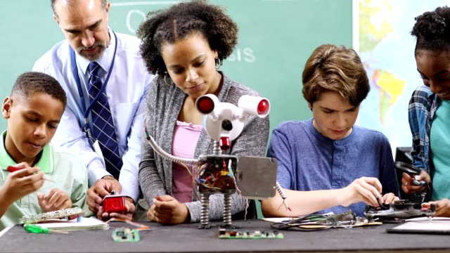 Junior high school age students build robot in technology, engineering class. video