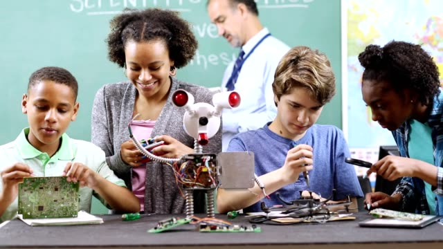 Junior high school age students build robot in technology, engineering class. Junior high school age, multi-ethnic group of teenagers work on building a robot in technology class in school classroom setting.  STEM topics.  Robot, circuit boards, tools seen on table.  Teacher in background. middle school teacher stock videos & royalty-free footage