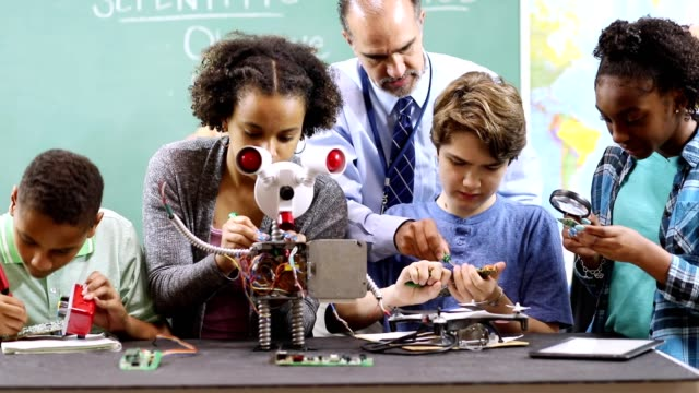 Junior high school age students build robot in technology, engineering class.