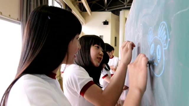 vídeos y material grabado en eventos de stock de estudiantes de secundaria que dibujan un dibujo en la pizarra - escuela media