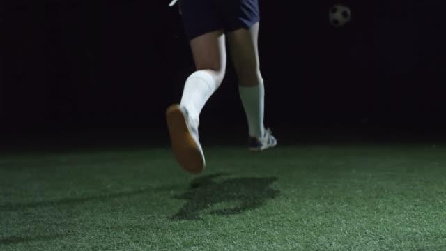 vídeos de stock e filmes b-roll de junior sportsman kicking soccer ball - liga desportiva