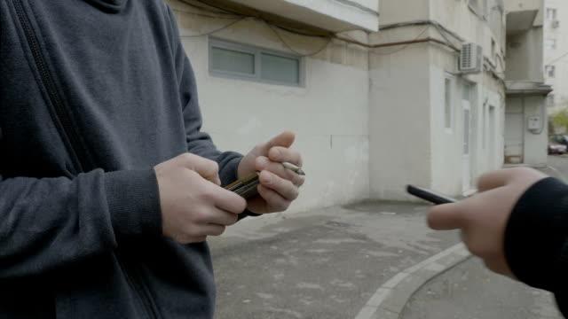 stockvideo's en b-roll-footage met junkie jongen in kap verkoop van drugs aan een jonge student die betaalt voor marihuana met behulp van de online bankieren van zijn smartphone - kids online abuse
