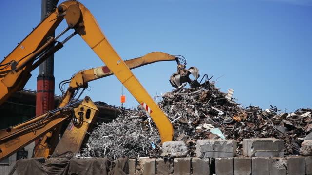 Junkyard claws sorting trash  construction machinery stock videos & royalty-free footage