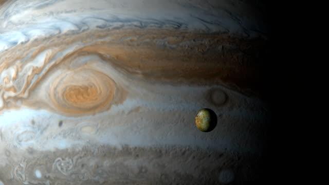 jupiter planet and io moon in the outer space - io księżyc filmów i materiałów b-roll
