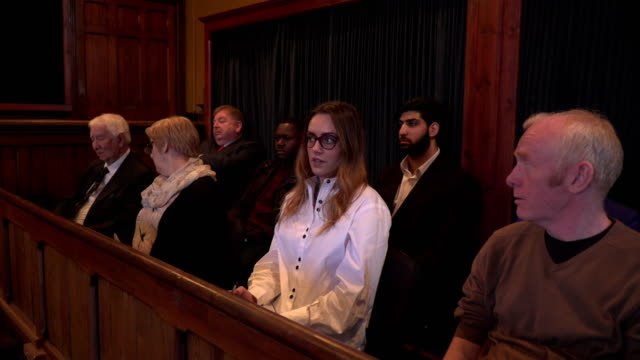 4K DOLLY: Jury looking unimpressed in a Courthouse Stock 4K video clip footage of a Jury sat listening to a legal case in the courtroom. The Jury is made up of different genders, ages and race. They look unimpressed with what the witness is saying. Filmed with a circular Dolly motion legal trial stock videos & royalty-free footage