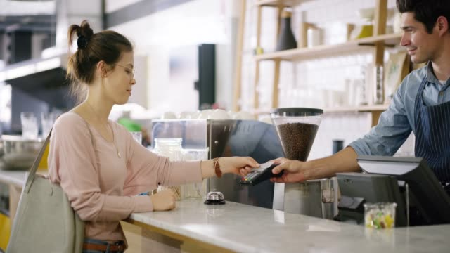 Just a simple tap completes the transaction 4k video of a customer paying for her bill using a credit card and NFC technology in a cafe credit card purchase stock videos & royalty-free footage