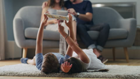 Just another great idea for what to do indoors 4k video footage of a young family using technological devices in the living room at home family stock videos & royalty-free footage