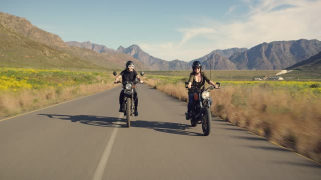 Just cruisin' 4k video footage of two attractive young women riding their motorcycles on the open road crash helmet stock videos & royalty-free footage