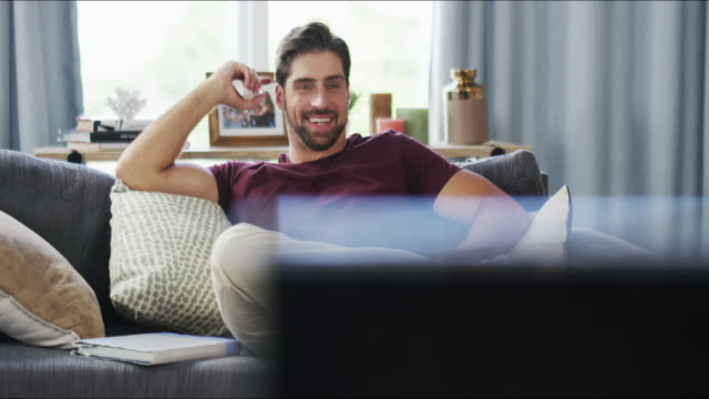 Just in time for my favourite show! 4k video footage of a handsome young man changing channels while watching tv in his living room at home watching tv stock videos & royalty-free footage