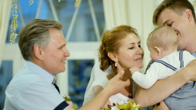 Just married adult couple kisses their grandson video