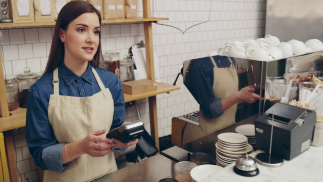 Just tap and pay 4k video footage of a young barista taking a credit card payment from a customer at a cafe paying stock videos & royalty-free footage