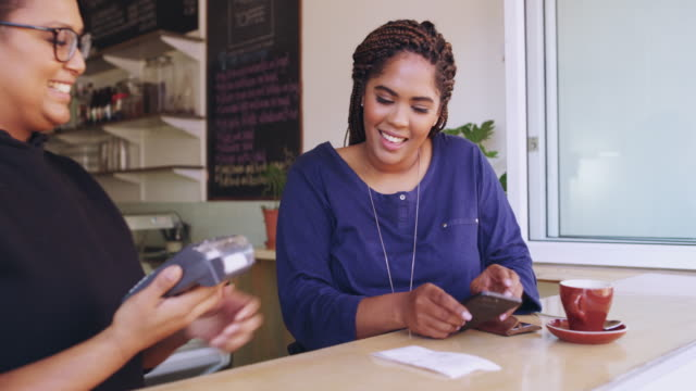 Just tap to transact 4k video of a customer paying for her bill using a credit card and NFC technology in a cafe tapping stock videos & royalty-free footage