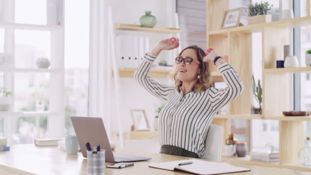 Just what I wanted 4k video footage of an attractive young businesswoman looking satisfied while working on a laptop in a modern office good news stock videos & royalty-free footage