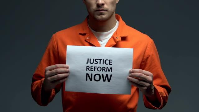justice reform now demanding on card in hands of caucasian prisoner, fairness - wine filmów i materiałów b-roll