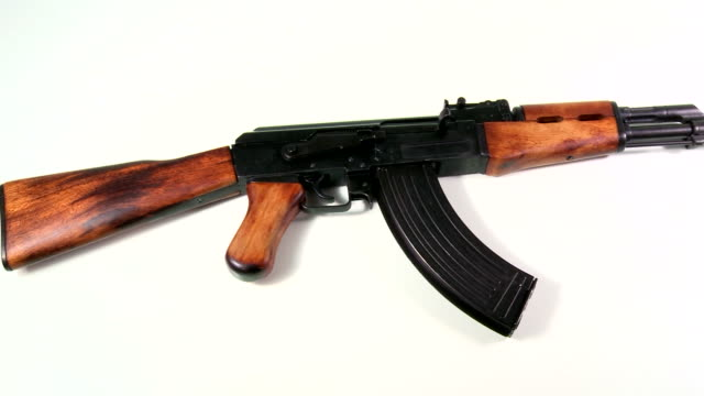 AK 47 Kalashnikov 1947, beauty-shot on white background, knee-shot of the body section with a slow pan from left to right, showing the barrel section and backwards. video