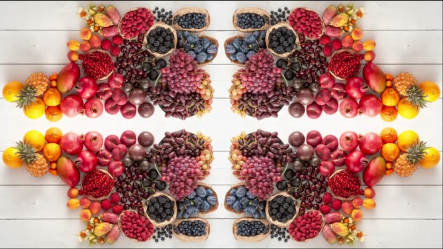 Kaleidoscope pattern made from colorful fruit selection. Playful Flat Lay Health Food Concept.