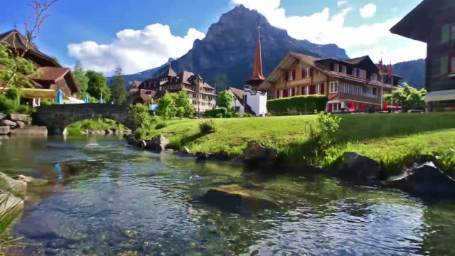 Kandersteg village in the Swiss alps - Summer The small town of Kandersteg in the Bernese Oberland region of Switzerland, a river running through a traditional town with a church and chalets and snow covered mountains in the background. chalet stock videos & royalty-free footage