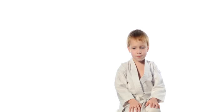 Karate boy exercising isolated against white background video