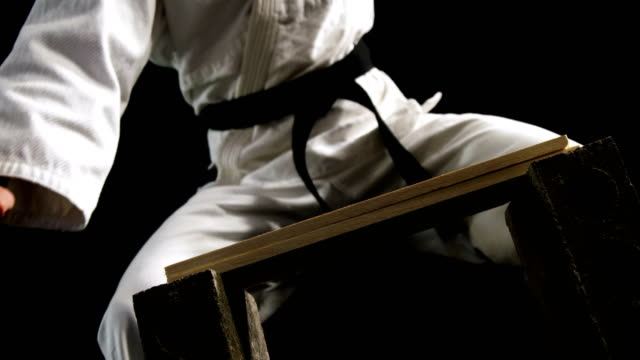 Karate man breaking wood Karate man breaking wood against black background martial arts stock videos & royalty-free footage