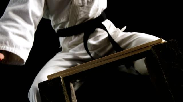 vídeos de stock, filmes e b-roll de homem da taxa de karatê que quebra a madeira - artes marciais
