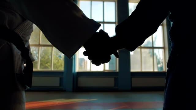 vídeos de stock, filmes e b-roll de o aperto de mão de dois atletas de karatê - artes marciais