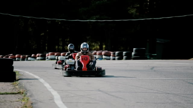 Kart drivers moving on a go kart track passing by the camera Go-kart track. Kart drivers moving on a go kart track passing by the camera. go cart stock videos & royalty-free footage