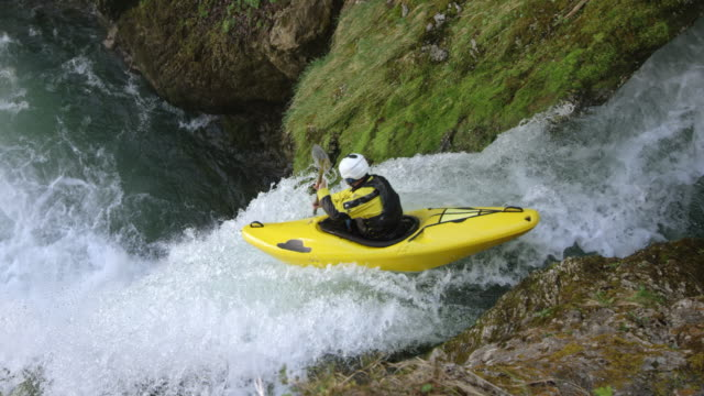 SLO MO Kayaker in a yellow kayak running a waterfall and diving into the plunge pool