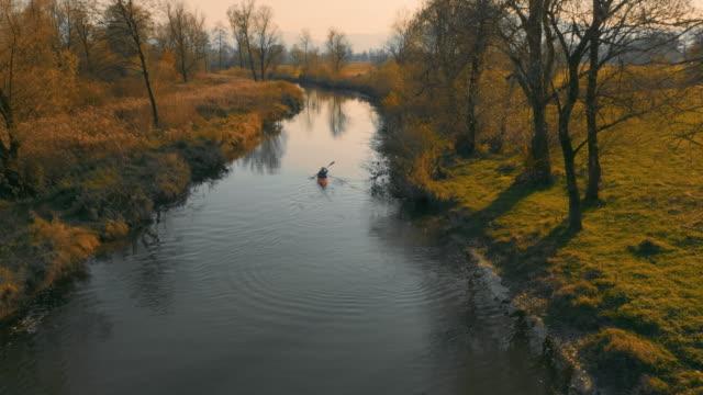 vídeos de stock, filmes e b-roll de kayaker em águas calmas no ensolarado dia de outono - caiaque
